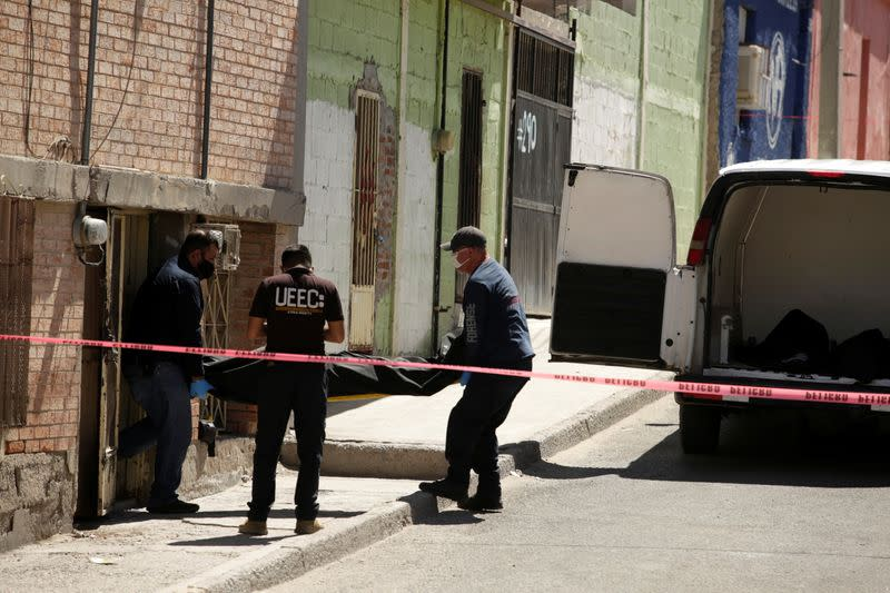 Forensic technicians remove a body from the crime scene where unknown assailants murdered a member of the LGBT community, in Ciudad Juarez