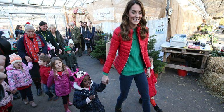 <p>Kate and a little girl hold hands as the duchess leads children to pick a Christmas tree.</p>