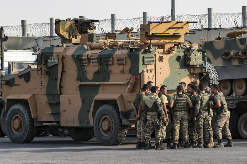 Turkish soldiers prepare to enter Syria aboard an armoured personnel carrier at the border with Syria in Karkamis, Gaziantep province, southeastern Turkey, Tuesday, Oct. 15, 2019. Turkey defied growing condemnation from its NATO allies to press ahead with its invasion of northern Syria on Tuesday, shelling suspected Kurdish positions near the border amid reports that Syrian Kurds had retaken a key town. (AP Photo/Emrah Gurel)
