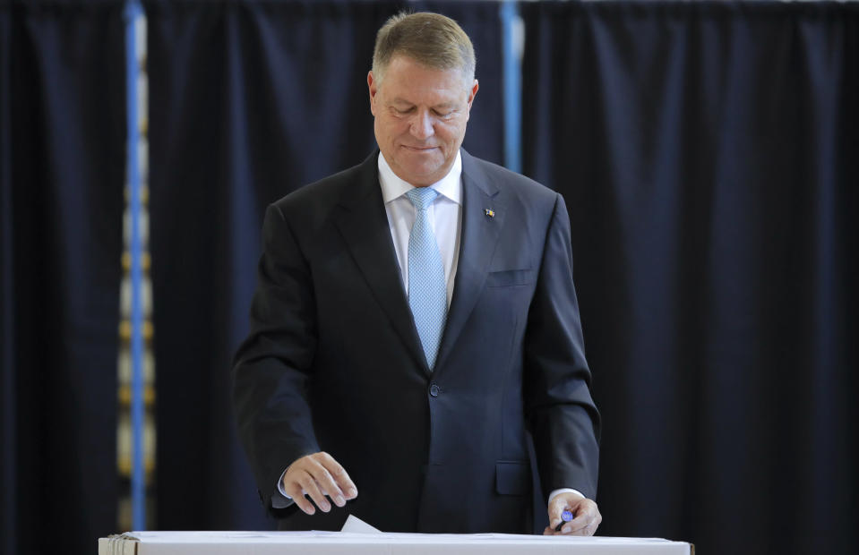 Romanian President Klaus Iohannis casts his vote in Bucharest, Romania, Sunday, Nov. 10, 2019. Voting got underway in Romania's presidential election after a lackluster campaign overshadowed by a political crisis which saw a minority government installed just a few days ago. (AP Photo/Vadim Ghirda)