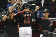 Arizona Diamondbacks' Nick Ahmed (13) is congratulated by teammate David Peralta, left, and manager Torey Lovullo, right, after scoring against the San Francisco Giants during the seventh inning of a baseball game Saturday, May 18, 2019, in Phoenix. (AP Photo/Ralph Freso)