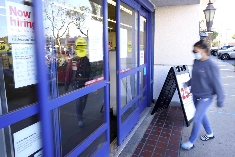 "A customer walks by a ""Now hiring"" sign as she enters a Staple's store, Tuesday, Feb. 2, 2021, in Simi Valley, Calif. Hiring has weakened for six straight months. Nearly 10 million jobs remain lost since the coronavirus struck. And this week, the Congressional Budget Office forecast that employment won't regain its pre-pandemic level until 2024. (AP Photo/Mark J. Terrill)"