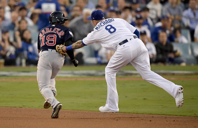 Los Angeles Dodgers shortstop Manny Machado, right, tags Boston Red Sox's Jackie Bradley Jr. in a run down during the third inning in Game 3 of the World Series baseball game on Friday, Oct. 26, 2018, in Los Angeles. (AP Photo/Mark J. Terrill)
