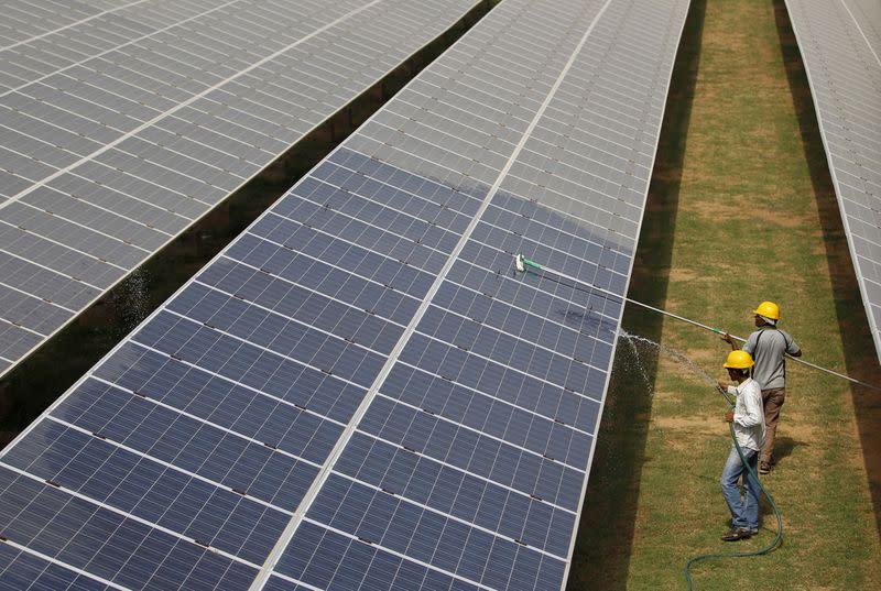 FILE PHOTO: Workers clean photovoltaic panels inside a solar power plant in Gujarat