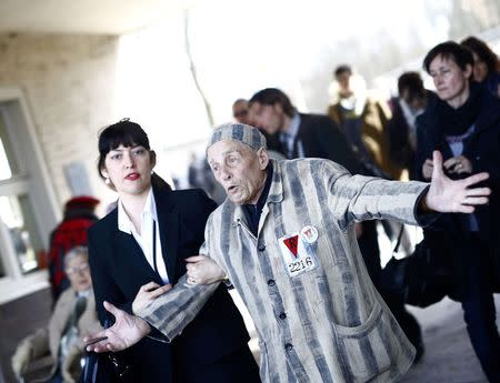 Survivor Alexander Butschuk gestures as he arrives to the former Nazi concentration camp Buchenwald near Weimar, April 12, 2015. REUTERS/Kai Pfaffenbach