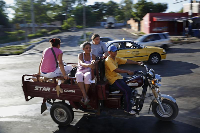 People use a motorcycle along Artigas Avenue in Asuncion, Paraguay, Thursday, Jan. 30, 2014. The city is phasing out horse-draw carts used by people who collect recyclable material and is sending the horses to an equine sanctuary. Horse-cart owners are being offered $350 per each horse as a first installment toward buying three-wheeled moto-carts that can replace the carriages. (AP Photo/Jorge Saenz)