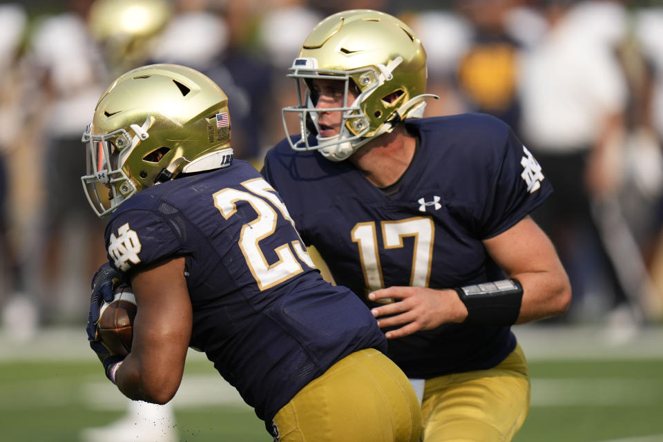 Notre Dame quarterback Jack Coan (17) hands off to running back Chris Tyree (25) in the second half of an NCAA college football game against Toledo in South Bend, Ind., Saturday, Sept. 11, 2021. Notre Dame won 32-29. (AP Photo/AJ Mast)