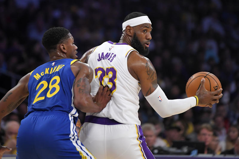 Los Angeles Lakers forward LeBron James, right, tries to move by Golden State Warriors forward Alfonzo McKinnie during the first half of a preseason NBA basketball game Wednesday, Oct. 16, 2019, in Los Angeles. (AP Photo/Mark J. Terrill)