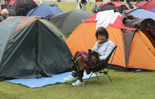 """In this Tuesday, July 9, 2019, a woman reads as she waits in a queue, as tennis fans wait in line for tickets to enter the Wimbledon Tennis Championships in London. For many the Wimbledon experience starts in a tent as they gather in a small park across from the tournament grounds to camp out, some for days, in the hope of getting a ticket to Centre Court as they are released each day. """"The Queue"""" is a decades-old tradition that has grown to become its own phenomenon.(AP Photo/Natasha Livingstone)"""