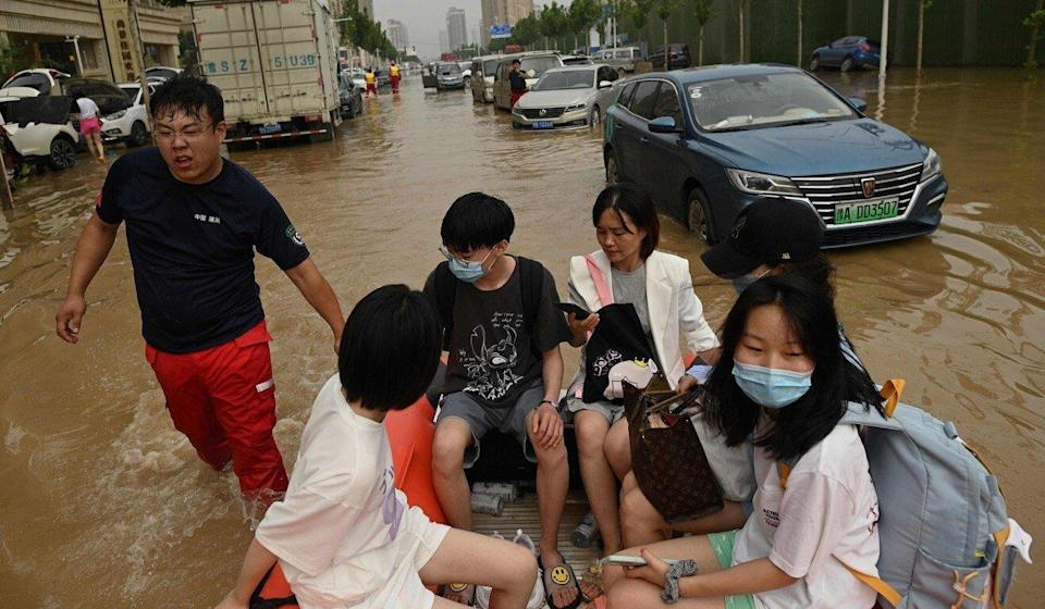 People ride on a rubber boat to cross a flooded street following heavy rain that flooded Henan province last week. Photo: AFP