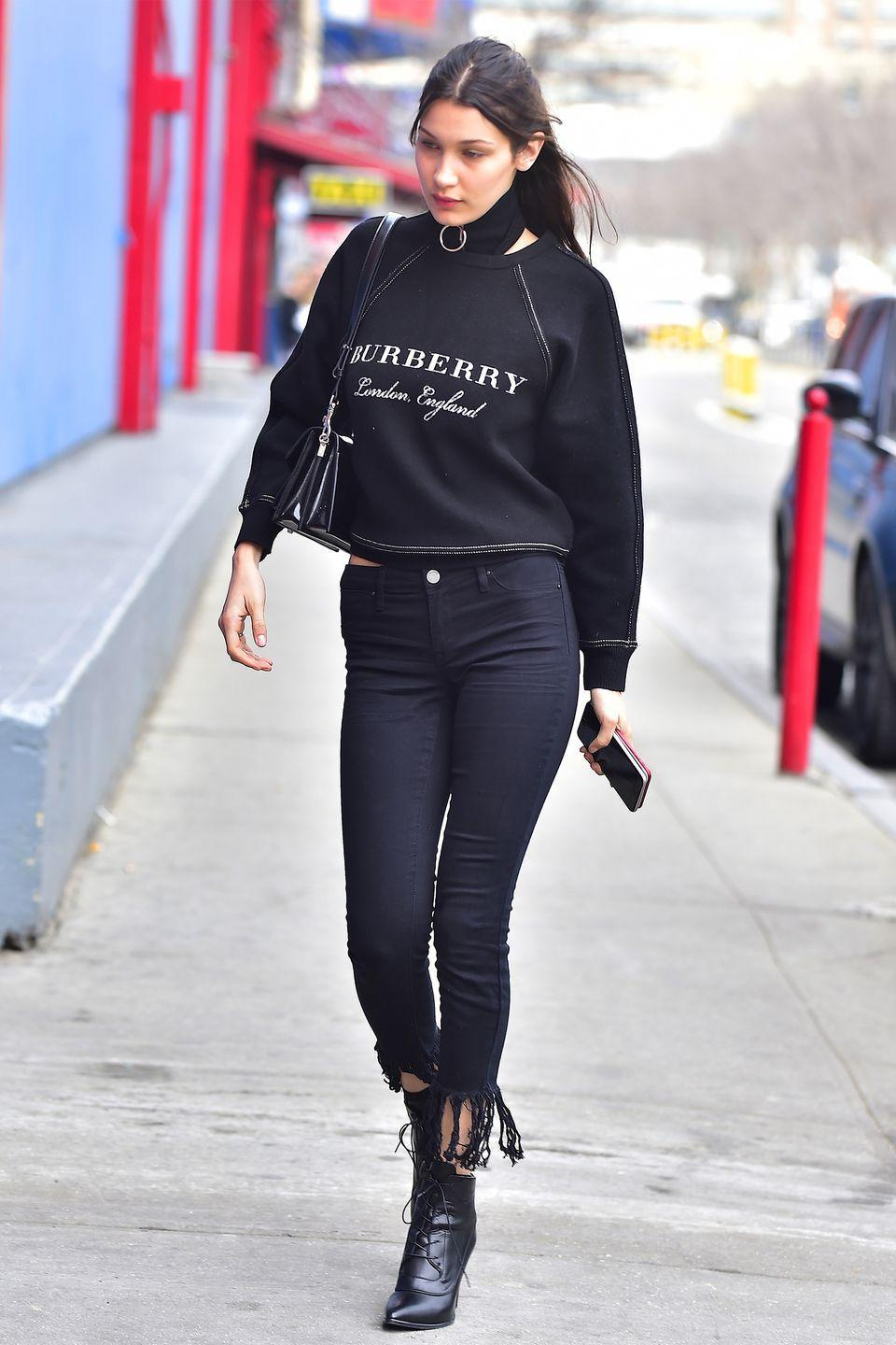 <p>In a Burberry sweatshirt, Blank NYC frayed black skinny jeans, Stuart Weitzman lace-up ankle booties and a black shoulder bag while out in New York.</p>