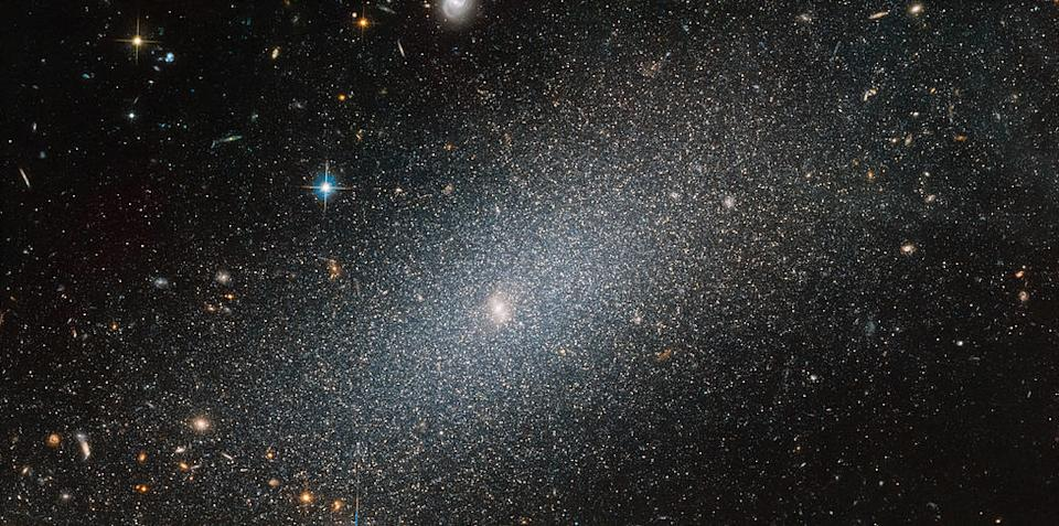 "A sparkling galaxy shines in this image from the NASA/ESA Hubble Space Telescope. The galaxy, known as PGC 29388, glimmers amidst a sea of more distant galaxies. It is a dwarf elliptical galaxy, named as such because it is ""small"" (relatively speaking) with ""only"" about 100 million to a few billion stars."