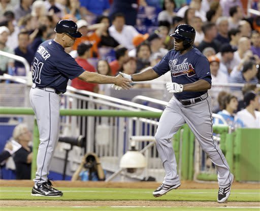 Atlanta Braves' Justin Upton, right, is congratulated by third base coach Brian Snitker after Upton hit a home run during the sixth inning of a baseball game against the Miami Marlins, Monday, April 8, 2013, in Miami. (AP Photo/J Pat Carter)
