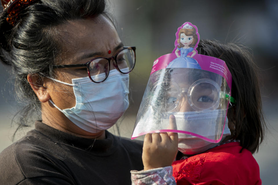 A Nepalese woman and her daughter wearing face masks as a precaution against the coronavirus watch devotees pull a chariot during the Rato Machindranath chariot festival in Lalitpur, Nepal, Saturday, May 15, 2021. A truncated version of a Hindu chariot festival took place in Nepal's capital on Saturday amid strict COVID-19 restrictions, following an agreement between organizers and authorities that prevented a repeat of violent confrontations between police and protesters at last year's festival. (AP Photo/Niranjan Shrestha)