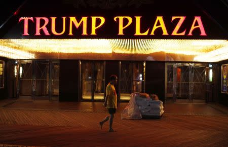 A man walks past sandbags ready to be used to protect Trump Plaza Casino from water damage on the boardwalk in Atlantic City, New Jersey in this file photo