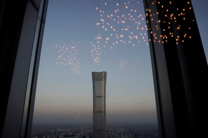FILE PHOTO: China Zun Tower under construction is seen through a window in Beijing's central business area
