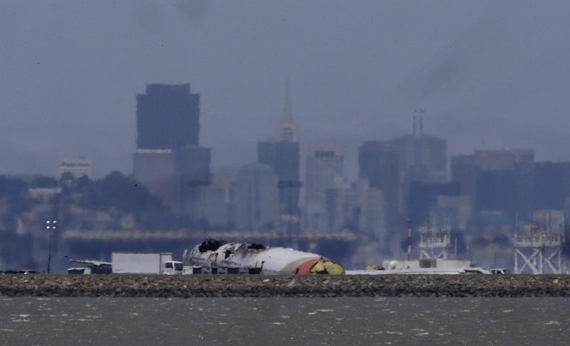 The wreckage of Asiana Flight 214, which crashed on Saturday, July 6, 2013, is seen on a tarmac in front of the San Francisco skyline at San Francisco International Airport in San Francisco, Wednesday, July 10, 2013. Investigators are struggling to piece together what went wrong in an accident that left two of the 307 aboard dead and close to 20 seriously injured. (AP Photo/Jeff Chiu)