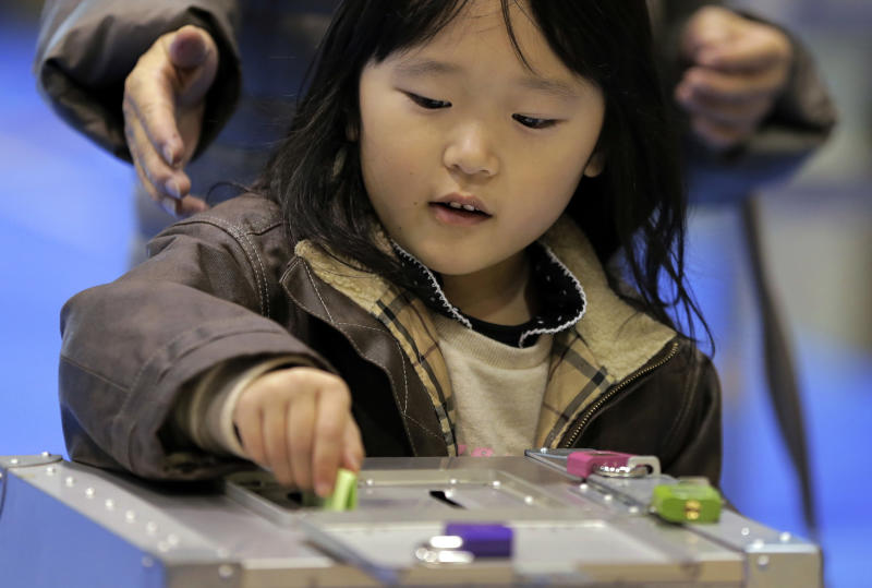 A girl places her mother's vote into a ballot box at a polling station in Tokyo, Sunday, Dec. 16, 2012. Voters cast their ballots in parliamentary elections which are likely to hand power back to a conservative party that ruled Japan for most of the post-war era. (AP Photo/Itsuo Inouye)