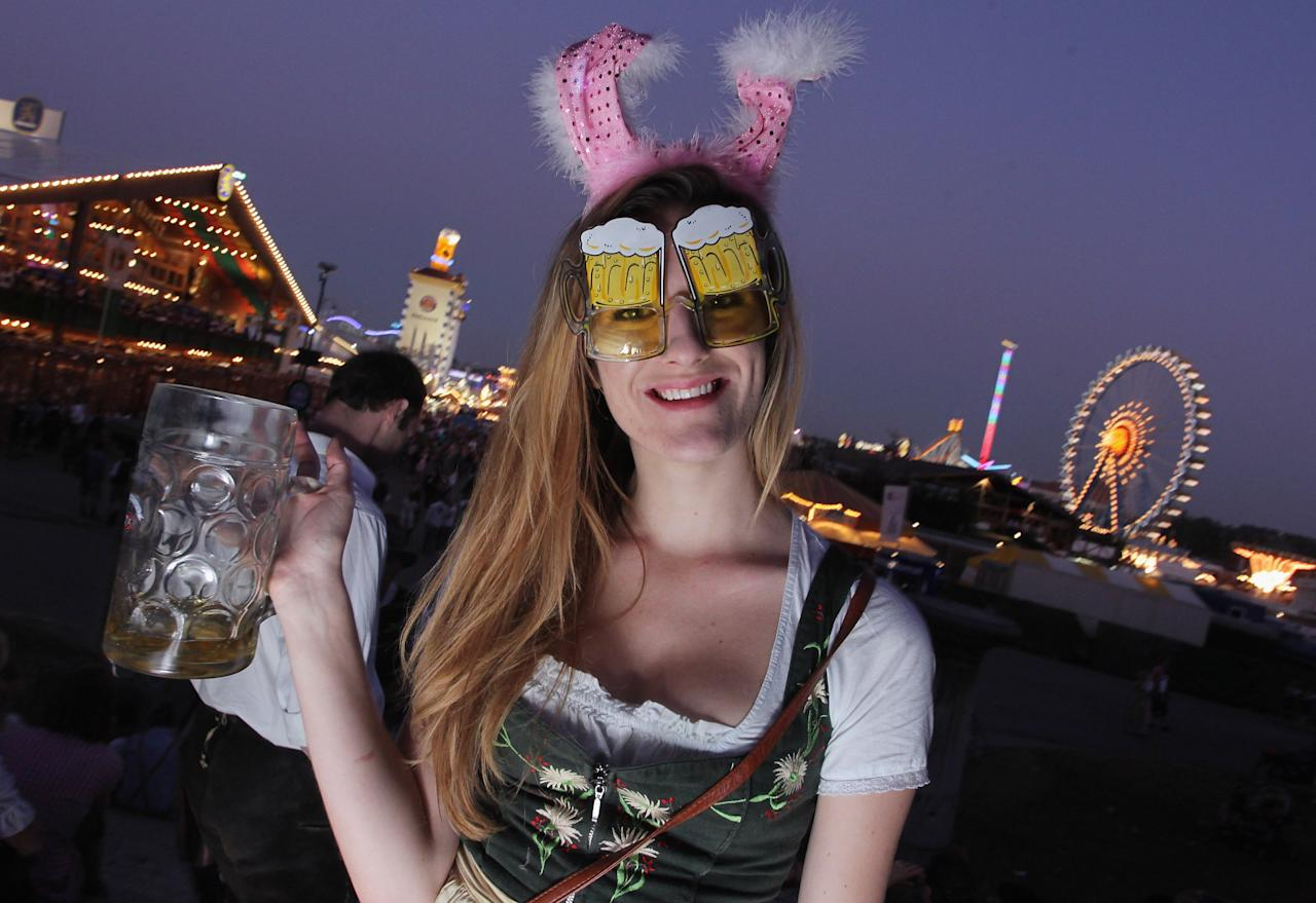 MUNICH, GERMANY - OCTOBER 03:  A young woman drinks beer while wearing a fancy costume during the last day of Oktoberfest beer festival on October 2, 2011 in Munich, Germany. The world's largest beer festival took place this year starting on September 17, running through to October 3.  (Photo by Johannes Simon/Getty Images)
