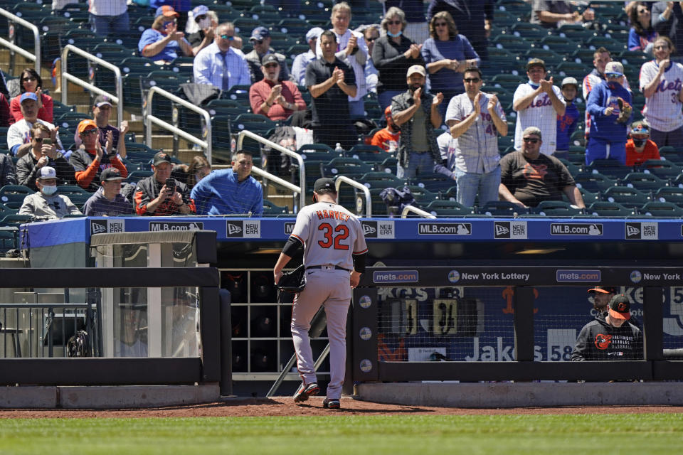 Fans stand and applaud Baltimore Orioles starting pitcher Matt Harvey (32) as he leaves the mound during the fifth inning of a baseball game against his former team, the New York Mets, Wednesday, May 12, 2021, in New York. (AP Photo/Kathy Willens)
