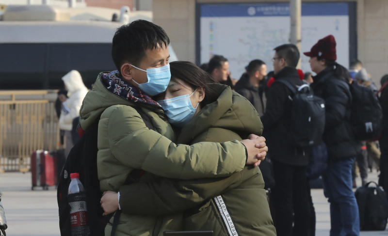A couple wearing masks hug in front of Beijing Station in Beijing, China on January 22, 2020, prior to China's Lunar New Year holiday. Source: The Yomiuri Shimbun via AP Images