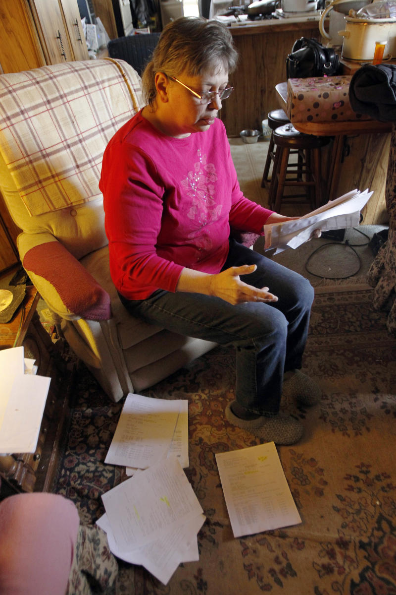 In this Thursday, Feb. 23, 2012 photo, Janet McIntyre sits with stacks of papers with water testing results  in her Evans City, Pa. home. McIntyre says state environmental officials refused to do follow-up tests after their lab reported her drinking water contained chemicals that could be from nearby gas drilling. (AP Photo/Keith Srakocic)