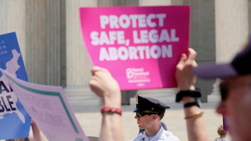 Protestors before US Supreme Court hold up placard for safe, legal abortion.