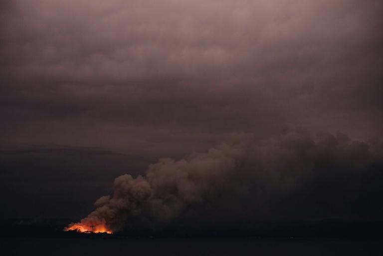 This handout photo taken on January 6, 2020 and received on January 7 from the Australian Department of Defence shows a fire in the distance seen from the Royal Australian Navy's HMAS Adelaide ship off the coast in Eden in New South Wales