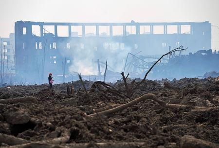 A woman walks at the site at the pesticide plant owned by Tianjiayi Chemical following an explosion, in Xiangshui county, Yancheng, Jiangsu province, China March 23, 2019. REUTERS/Aly Song