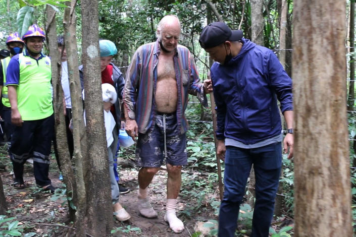 Rescuers lead Barry Leonard Weller, 72, out of the jungle, in Thailand's northeastern Khon Kaen province, Friday, Sept. 3, 2021. A 72-year-old British man has been found safe three days after disappearing in a thick jungle in northeastern Thailand while going to visit friends on a motorbike. A member of a local volunteer team that helped rescue him said a hunter came across Barry Leonard Weller in a remote forest in Khon Kaen province. He was asleep on a rock formation after climbing it to try to see a route out. (AP Photo/Tanadon Sribura )