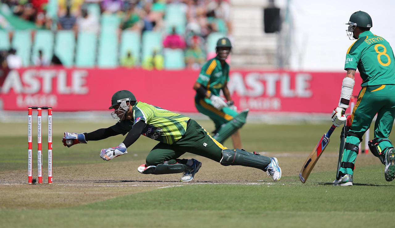 Pakistan's Kamran Akmal dives to stop the ball on March 21, 2013 during the fourth one-day international against South Africa at Kingsmead in Durban.                  AFP PHOTO  / Stringer        (Photo credit should read -/AFP/Getty Images)