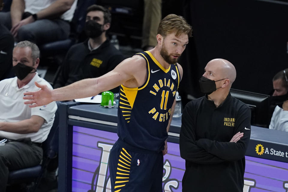 Indiana Pacers' Domantas Sabonis talks with coach Nate Bjorkgren during the second half of the team's NBA basketball game against the Milwaukee Bucks, Thursday, May 13, 2021, in Indianapolis. (AP Photo/Darron Cummings)