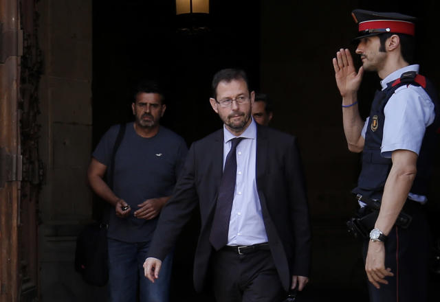 A Mosso D'Esquadra (Catalan regional police officer) salutes Spanish anti-corruption prosecutor José Grinda, center, as he leaves the Generalitat de Catalunya (Catalan government) in Barcelona in 2017. (Photo: Pau Barrena/AFP/Getty Images)