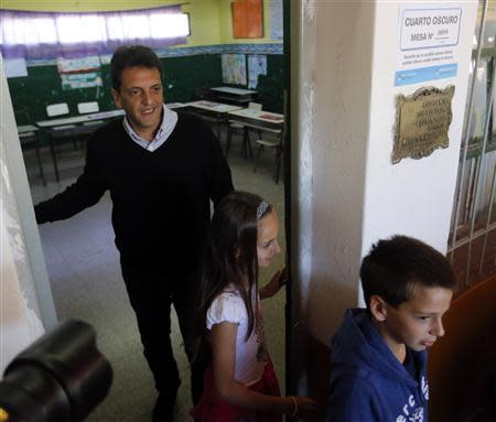 Sergio Massa, mayor of Buenos Aires' Tigre, accompanied by his children Milagros and Tomas (R) prepares to vote for the legislative election in Tigre October 27, 2013. REUTERS/Enrique Marcarian