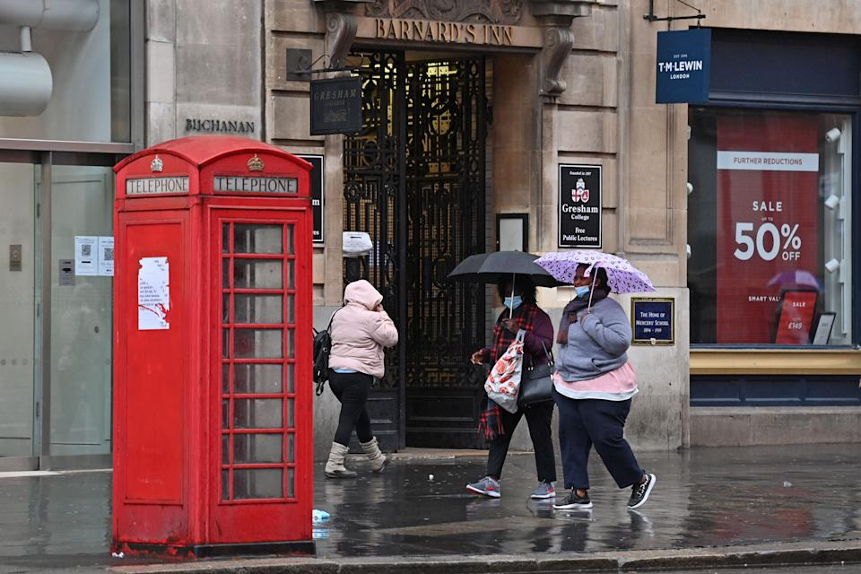 People wearing protective face masks, shelter from the rain under umbrellas as they walks along Holborn in central London on October 21, 2020, as the government considers further lockdown measures to combat the rise in novel coronavirus COVID-19 cases. - Britain has suffered Europe's worst death toll from coronavirus, with nearly 44,000 deaths within 28 days of a positive test result. After a summer lull, cases are rising again as in other parts of the continent -- and so are deaths, with 241 reported on Tuesday alone. (Photo by JUSTIN TALLIS / AFP) (Photo by JUSTIN TALLIS/AFP via Getty Images)