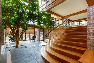At the center of the home is a three-story atrium with stone flooring, soaring windows and natural trees, allowing for a graceful interplay between the outdoors and interiors. Ample natural light accents the handsome, exposed brick and wood finishes throughout. More at NewJerseyLuxuryAuction.com.