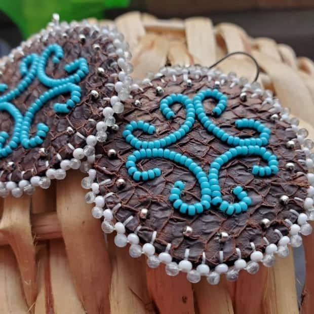 Travers used salmon skin to make the leather for these beaded petroglyph earrings. (Submitted by Nicole Travers - image credit)
