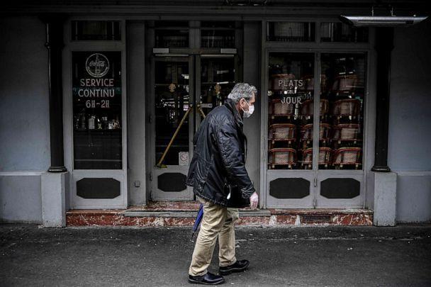 PHOTO: A man wearing a protective face mask walks past a closed restaurant in Paris on May 4, 2020, on the 49th day of France's nationwide lockdown aimed at curbing the spread of the novel coronavirus. (Christophe Archambault/AFP via Getty Images)