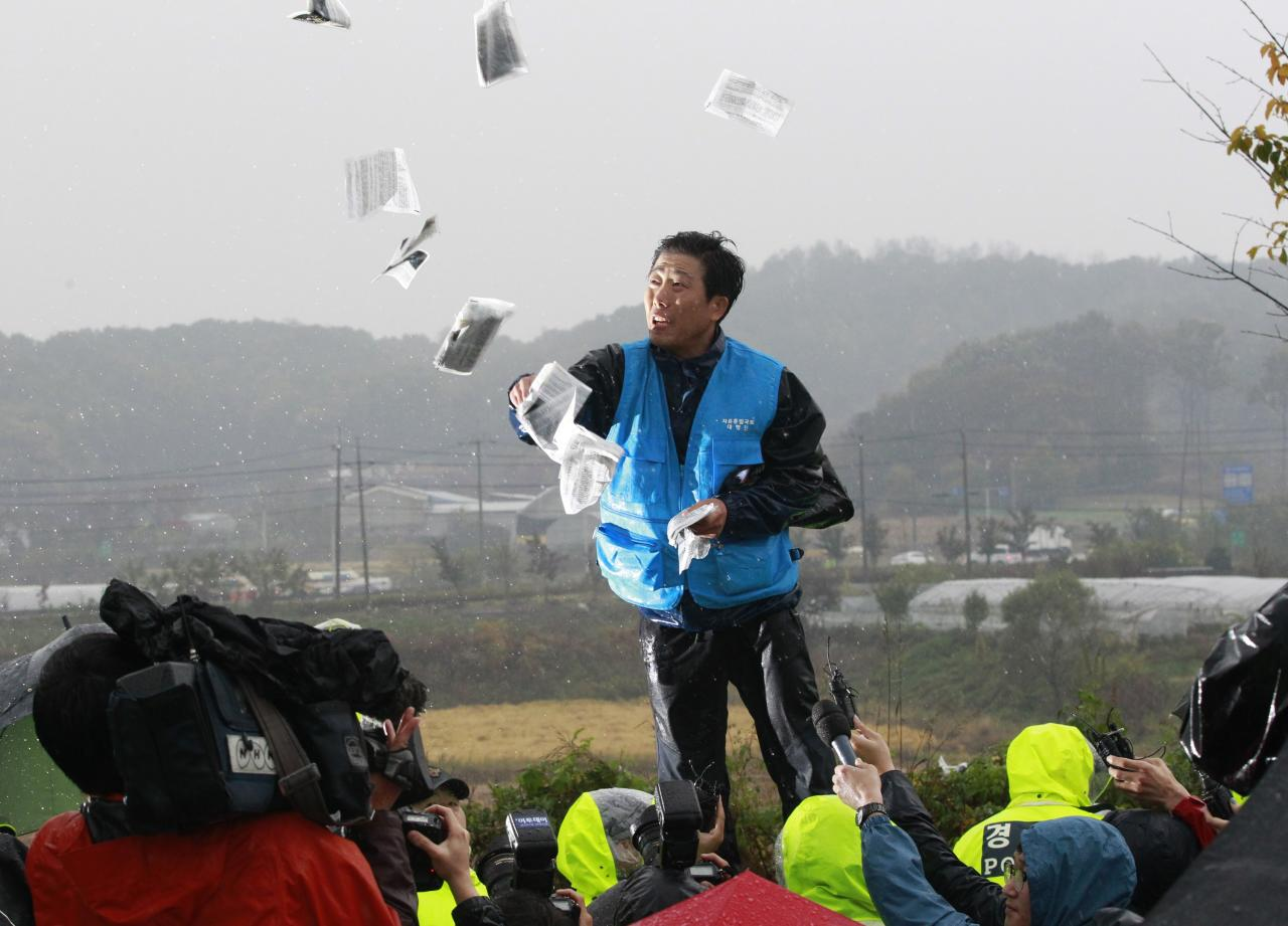North Korean defector Park Sang-hak hurls anti-North Korea leaflets as police block his planned rally on a road in Paju near demilitarized zone, South Korea Monday, Oct. 22, 2012. South Korea has banned activists from launching propaganda leaflets to North Korea after North Korea threatened to attack.(AP Photo/Ahn Young-joon)