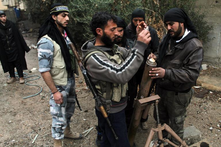 Rebel fighters inspect a mortar in the northeastern Syrian city of Deir Ezzor on December 31, 2013