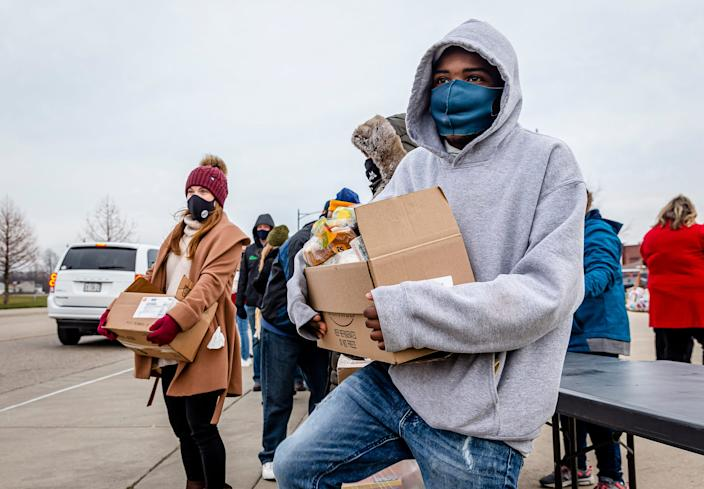 Djay Harris balances a box of food as he waits for the next car to pull up Dec. 18 in Jacksonville, Ill., as volunteers distribute food to anyone in need for the Central Illinois Foodbank.