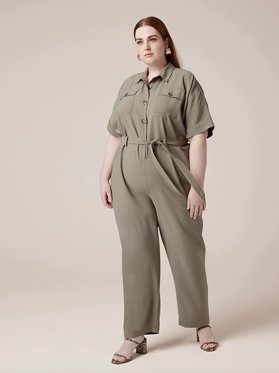 red head plus size model in tan belted jumpsuit and sandals