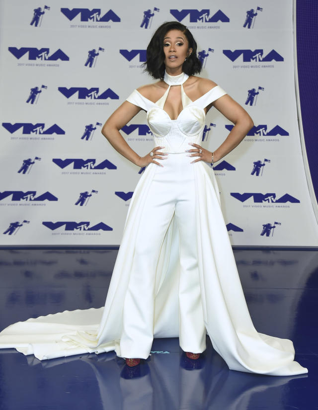 """<p>The rapper, who performed her hit """"Bodak Yellow"""" at the pre-show, wore a white jumpsuit with an attached train that was reminiscent of <a href=""""https://www.yahoo.com/style/michelle-obama-and-lady-gaga-have-something-in-162402420.html"""" data-ylk=""""slk:Lady Gaga's Brandon Maxwell look at the Oscars;outcm:mb_qualified_link;_E:mb_qualified_link"""" class=""""link rapid-noclick-resp newsroom-embed-article"""">Lady Gaga's Brandon Maxwell look at the Oscars</a>. (Photo: AP) </p>"""