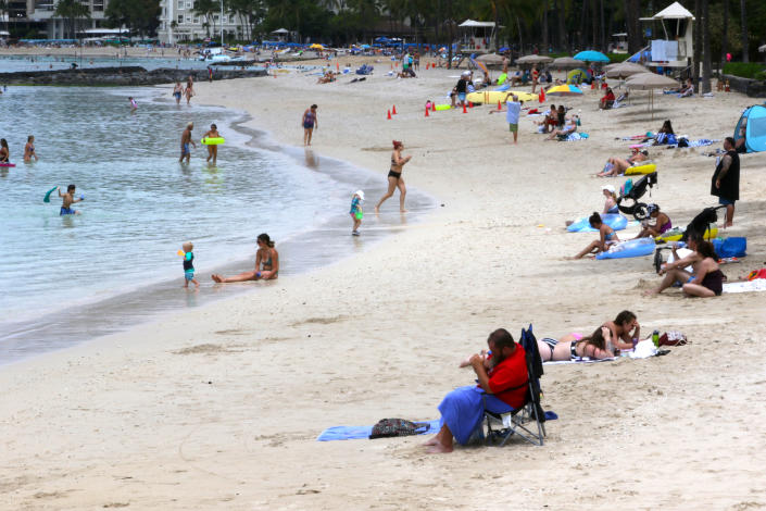 People gather on Waikiki Beach in Honolulu, Tuesday, Aug. 24, 2021. Hawaii was once seen as a beacon of safety during the pandemic because of stringent travel and quarantine restrictions and overall vaccine acceptance that made it one of the most inoculated states in the country. But the highly contagious delta variant exploited weaknesses as residents let down their guard and attended family gatherings after months of restrictions and vaccine hesitancy lingered in some Hawaiian communities.(AP Photo/Caleb Jones)