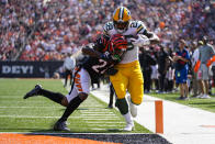 Green Bay Packers running back A.J. Dillon (28) runs in for a touchdown as he's hit by Cincinnati Bengals safety Vonn Bell (24) in the first half of an NFL football game in Cincinnati, Sunday, Oct. 10, 2021. (AP Photo/AJ Mast)