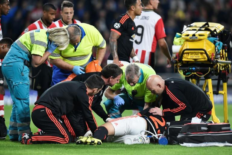 Manchester United defender Luke Shaw receives treatment for a double fracture of the leg during the UEFA Champions League football match between Eindhoven and Manchester United at the Philips stadium on September 15, 2015