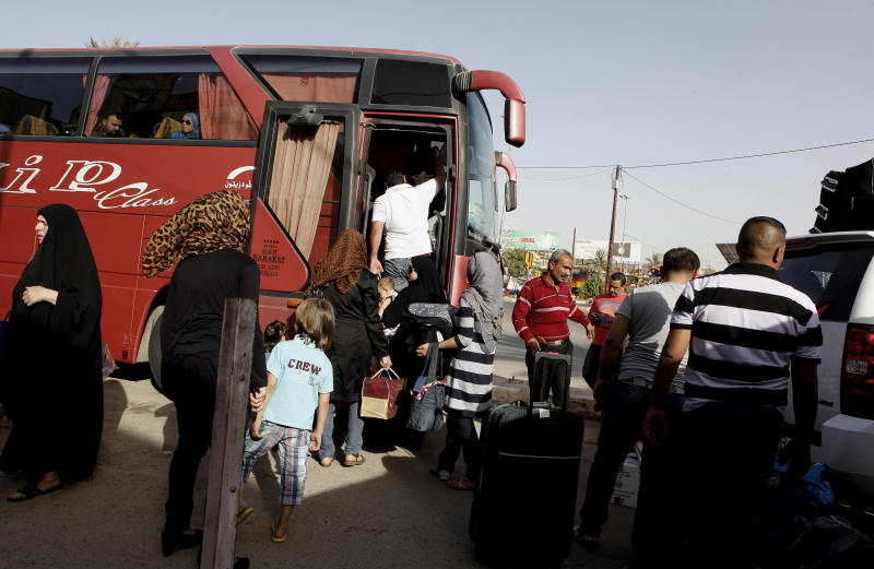 Syrian refugees leave Iraq to Syria to reunite with their families at a bus station in Baghdad, Iraq, Tuesday, June 11, 2013. Signs are growing that stretches of Iraq and Syria are morphing into a single battlefield for militants, exacerbating Iraq's slide into renewed deadly chaos a decade after Saddam Hussein's fall. Iraqi border posts are coming under attack, fighters are criss-crossing the frontier, and Syrian truck drivers and soldiers have been slain by militants inside Iraq. It's happening as the drumbeat of violence inside Iraq surges to levels not seen in half a decade _ back when U.S. troops were still here to help keep the peace. (AP Photo/ Hadi Mizban)