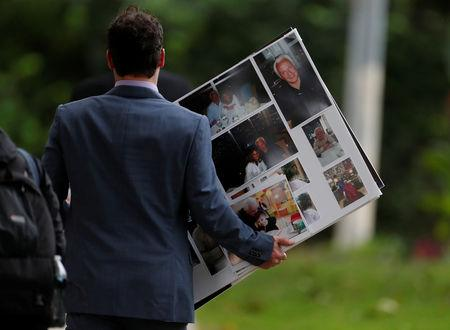 A mourner carries a poster board with family photos of Irving Younger, 69, a victim of Saturday's synagogue shooting, after his funeral at Rodef Shalom Temple in Pittsburgh, Pennsylvania, U.S., October 31, 2018. REUTERS/Cathal McNaughton