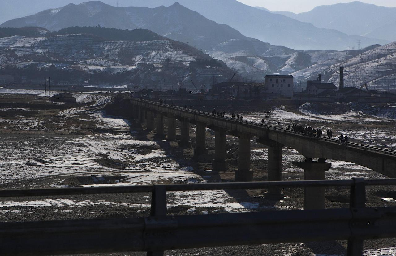 North Koreans cross a railroad bridge over a riverbed south of Mount Myohyang, and north of the capital city of Pyongyang, North Korea, Saturday, Feb. 23, 2013. (AP Photo/David Guttenfelder)