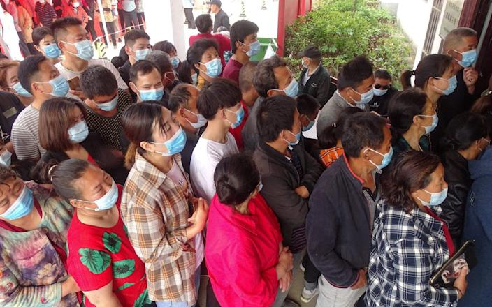 People queues to receive the vaccine in Linquan county, Fuyang city, in China's eastern Anhui province - AFP